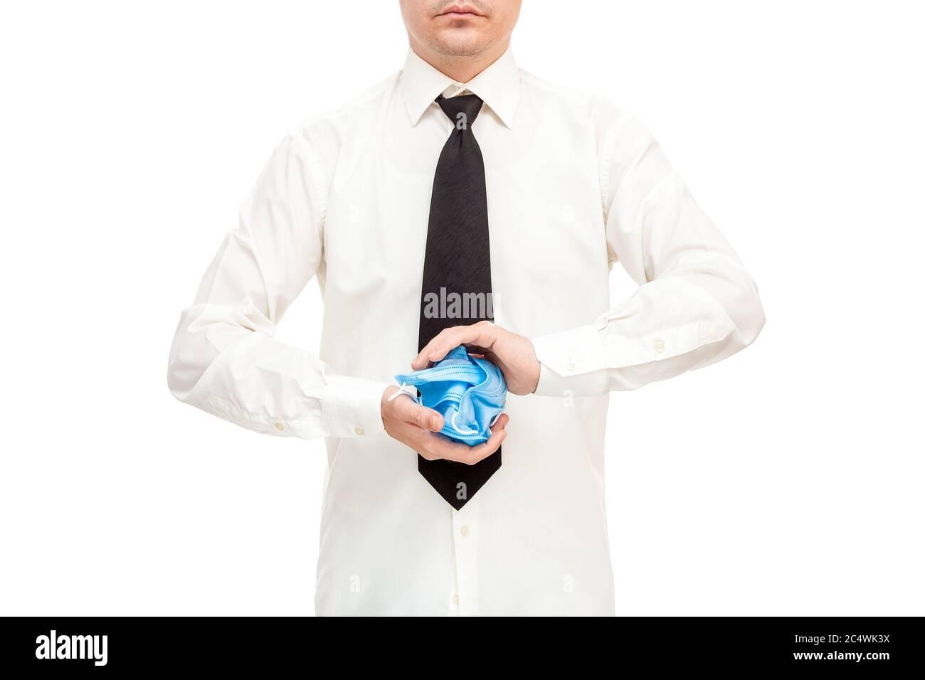 uomo senza volto in camicia bianca e cravatta nera sbriciolato mazzo di maschere mediche inefficaci e inutili nelle sue mani in protesta contro i crisi di quarantena Foto Stock
