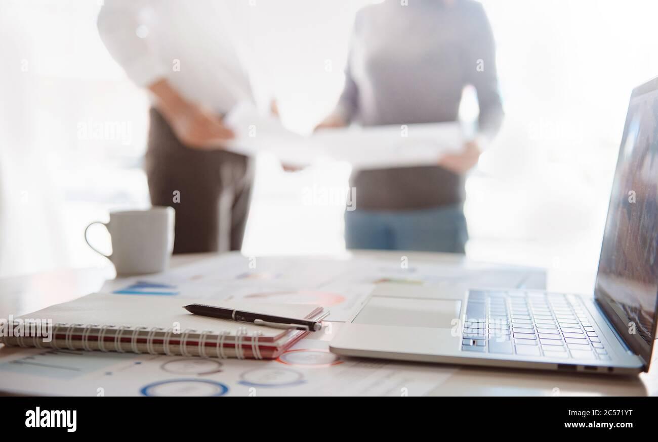Sfocatura immagine ravvicinata di una penna e di un computer che visualizzano dati finanziari, gruppo aziendale in background Foto Stock