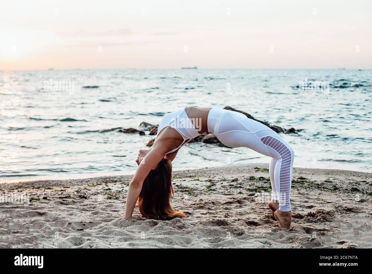 Vista laterale di una giovane donna in piedi in posizione Guerrior yoga sulla spiaggia di sabbia Foto Stock