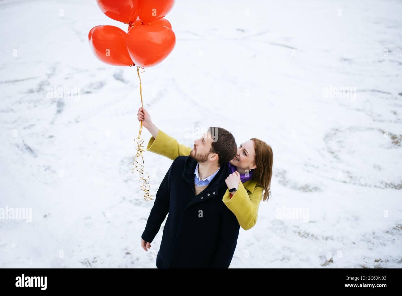 coppia caucasica fate una passeggiata in strada invernale, celebrando saint valentines giorno all'aperto. felice uomo e donna con palloncini d'aria rossa, su un romantico dat Foto Stock