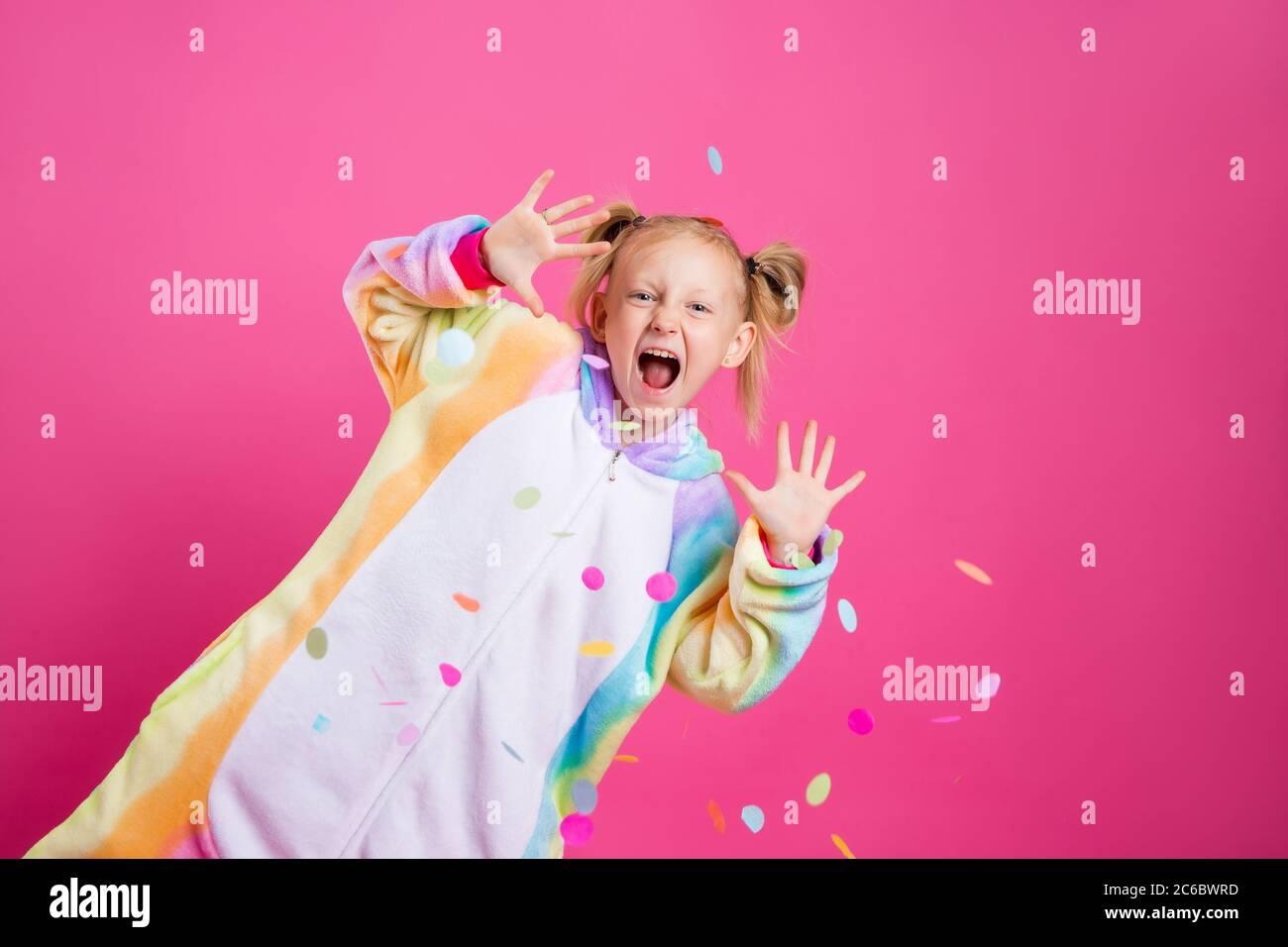 Felice bambina in kigurumi unicorn su sfondo rosa gioisce in confetti multicolore, spazio per il testo Foto Stock
