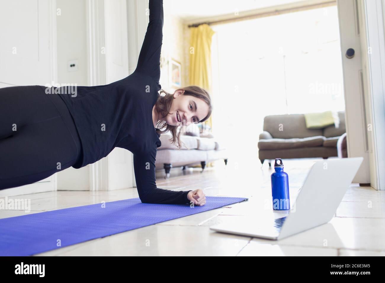 Adolescente ragazza che pratica yoga online al computer portatile a casa Foto Stock