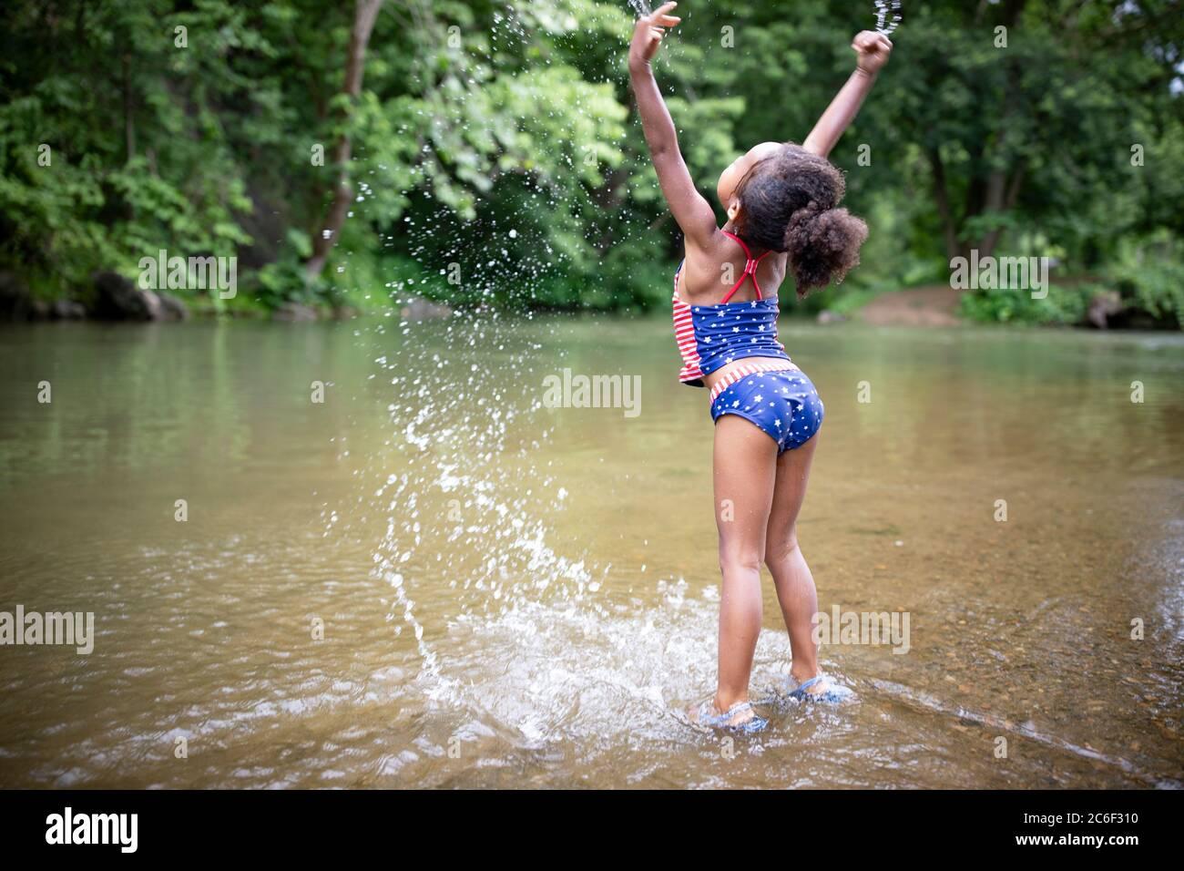 Una giovane ragazza si dilata e si spruzzi nel fiume Shenandoah, Virginia, USA. Foto Stock