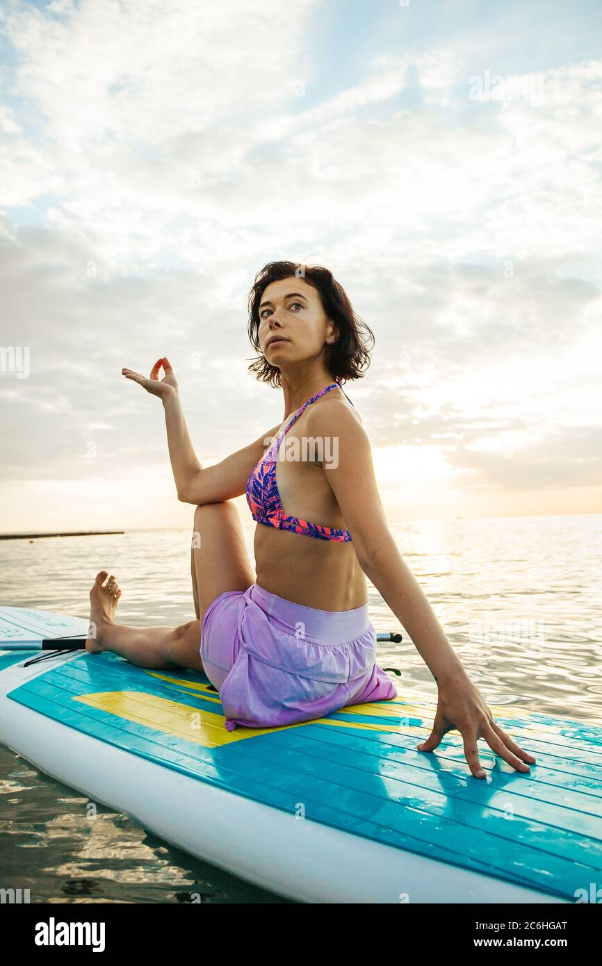 Giovane donna che fa YOGA su una tavola SUP nel lago all'alba Foto Stock