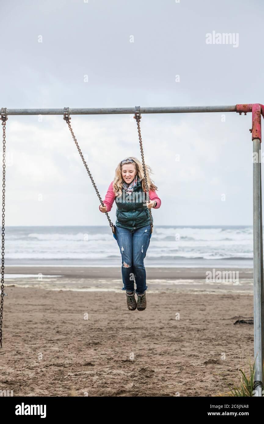 Una donna di mezza età che oscilla su un'altalena impostata a Seaside Beach, Oregon, USA. Foto Stock
