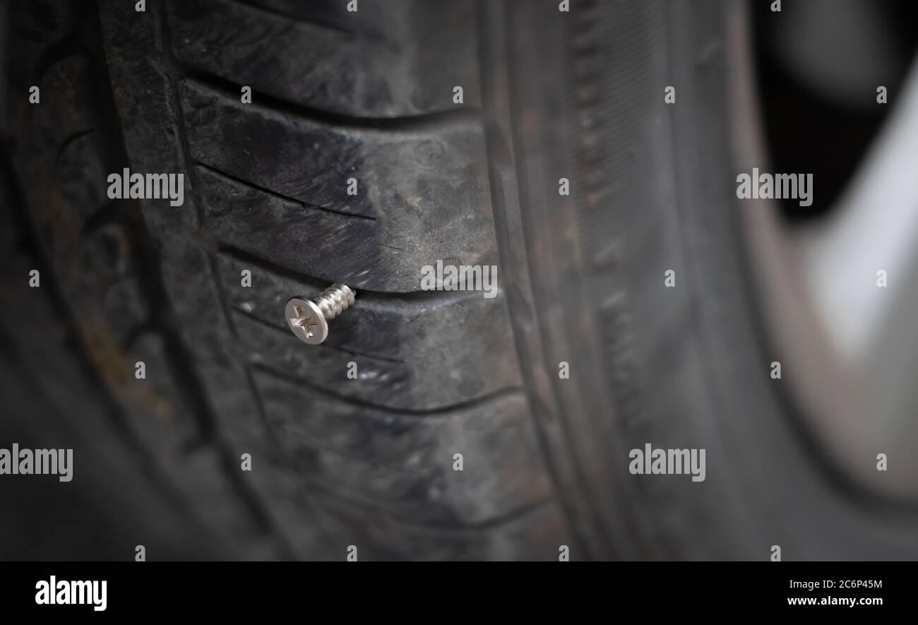 Primo piano chiodo metallico a vite con testa a bottone bloccato per forare lo pneumatico della ruota Foto Stock