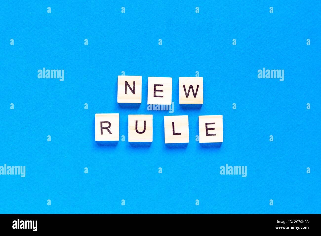 La NUOVA REGOLA è scritta in lettere di legno su sfondo blu. Nuovo concetto. Affari, legge, regole, aggiorna. Layout tflat. Op view. Foto Stock