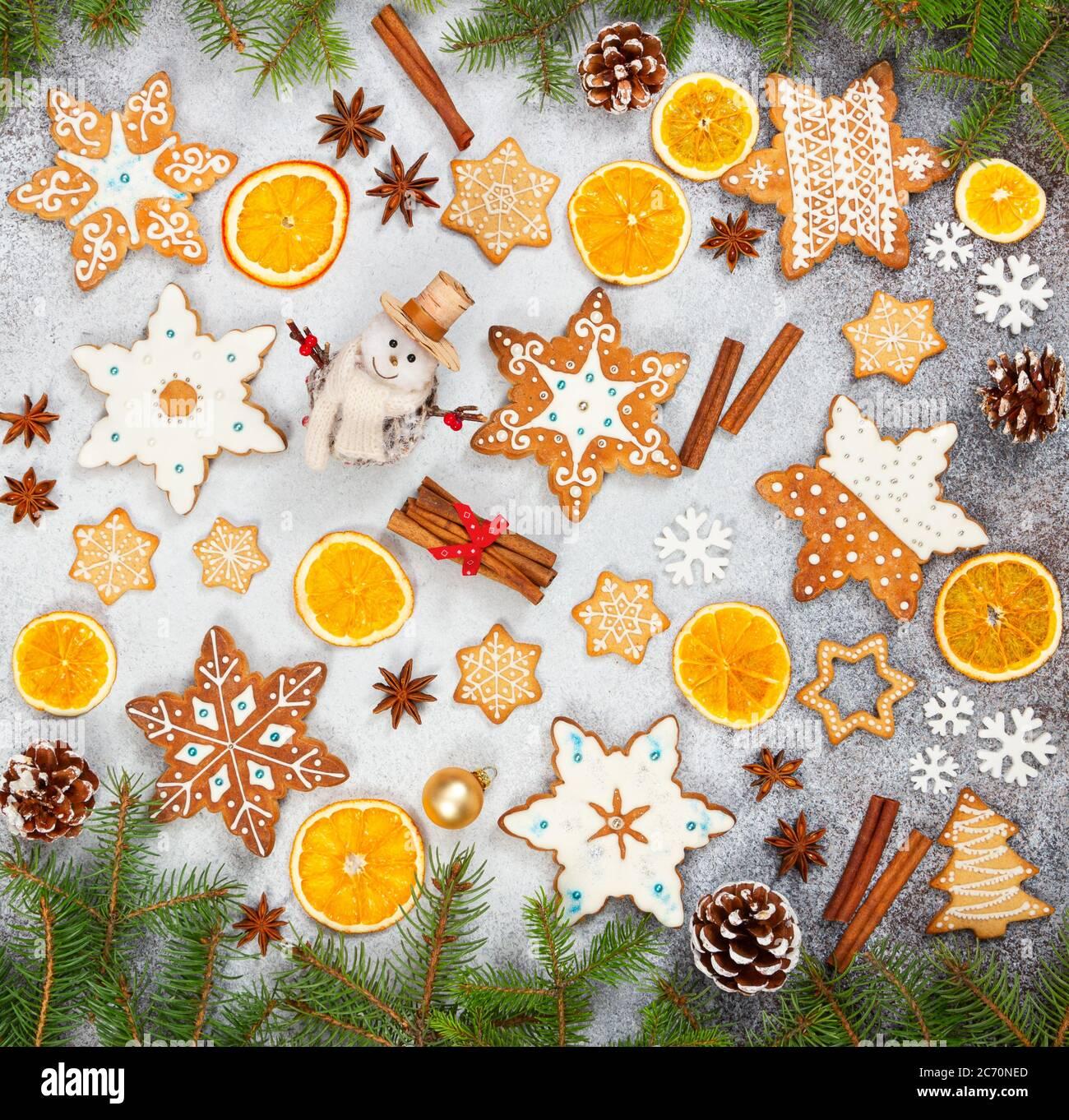 Biscotti allo zenzero natalizio in forma di fiocchi di neve, arancio secco, anice stellato e pupazzo di neve su fondo di pietra grigia. Vista dall'alto. Simboli di Capodanno e Chr Foto Stock