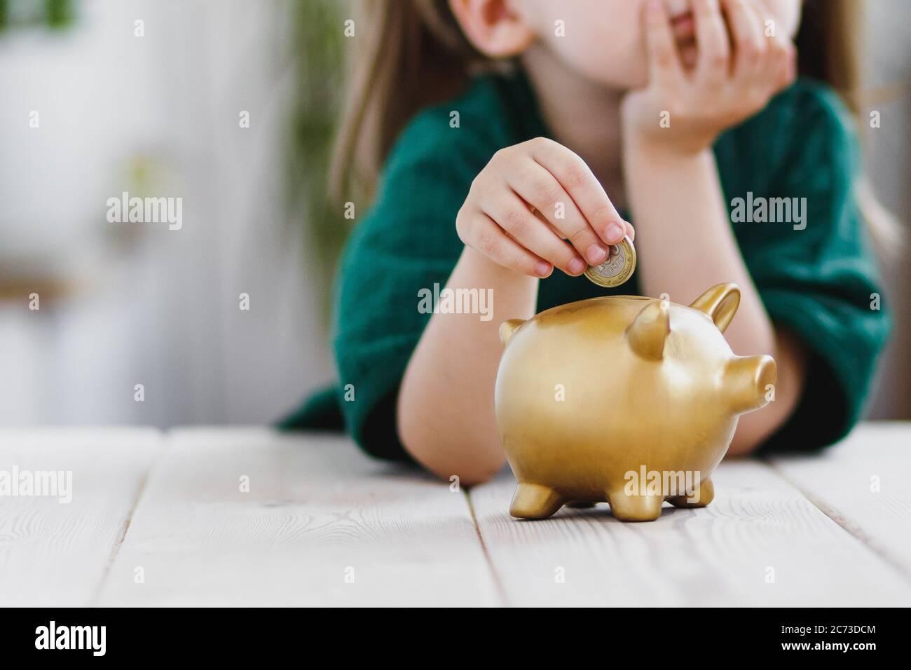 Bambina in abito verde pensando alla sua spesa di soldi e mettere una moneta in una banca piggy. Concetto di risparmio di denaro Foto Stock
