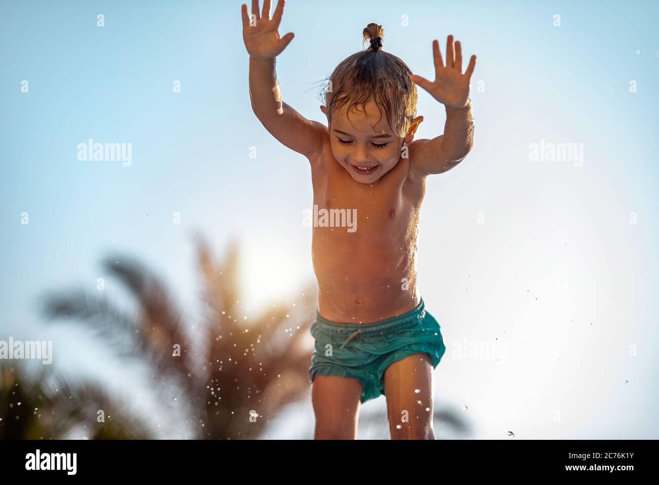 Bambino allegro con piacere divertirsi all'aperto. Little Boy che salgono in piscina. Divertirsi all'Aqua Park. Vacanze estive attive. Foto Stock