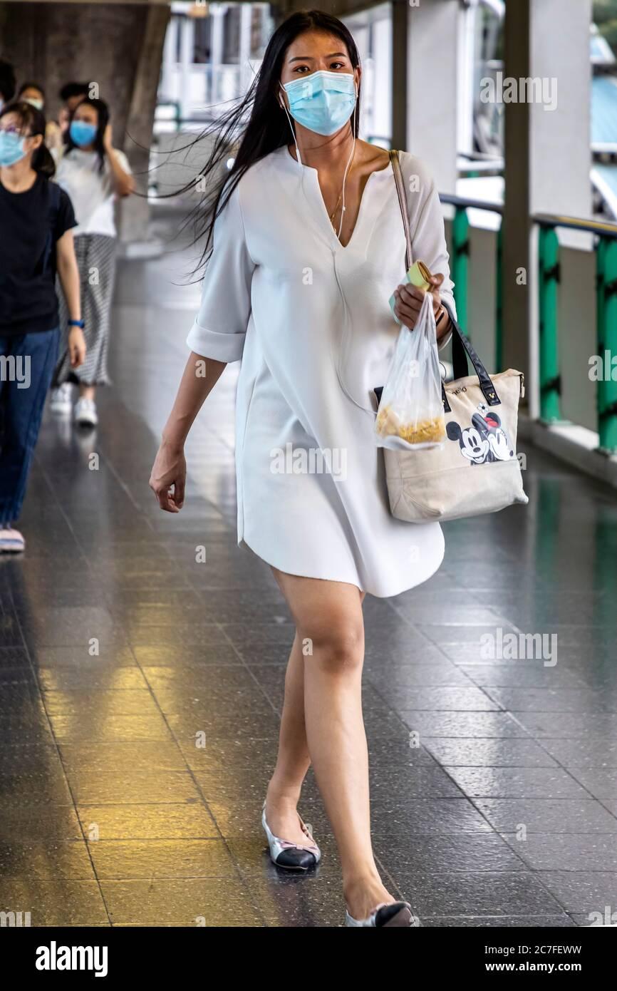 Donna che indossa maschera e auricolari che cammina per strada durante la covid 19 pandemia, Bangkok, Thailandia Foto Stock