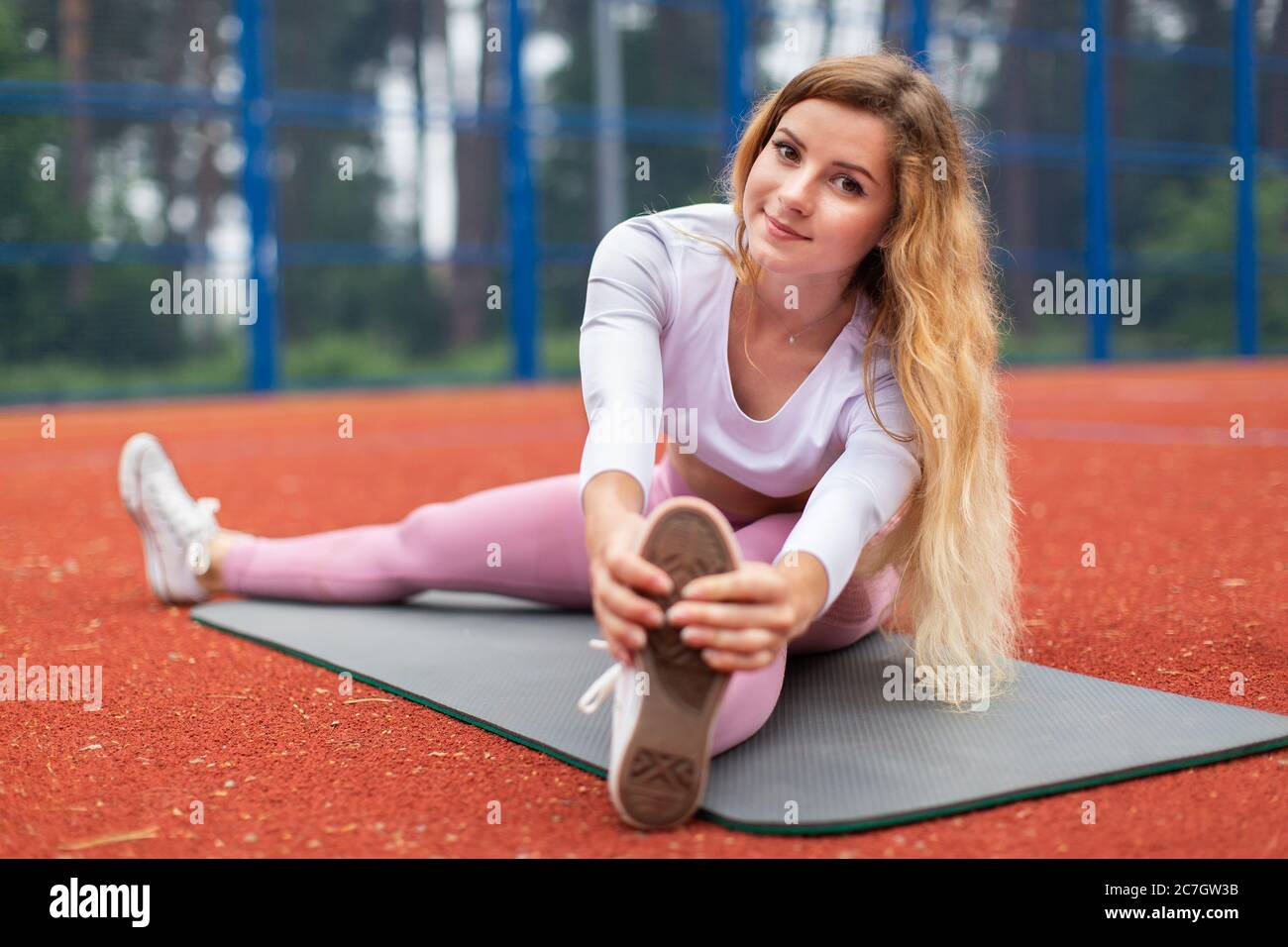 Ritratto di sorridente bella donna bionda che si stretona prima di fitness e yoga. Donna in abbigliamento sportivo rosa che fa esercizio di stretching, seduta sul tappetino Foto Stock