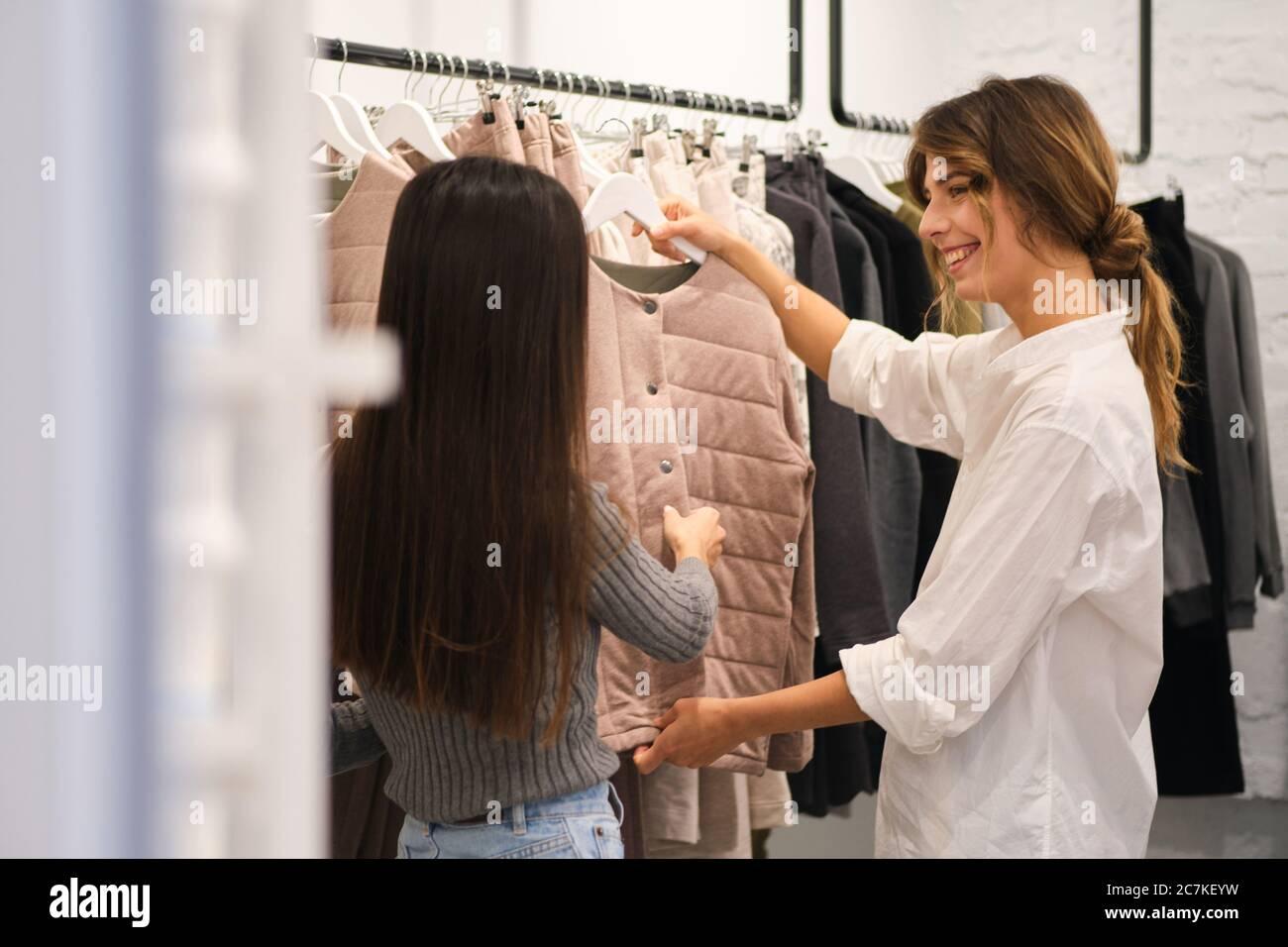 Giovane attraente designer che aiuta a scegliere i vestiti dalla nuova collezione alla bella ragazza in negozio di vestiti Foto Stock