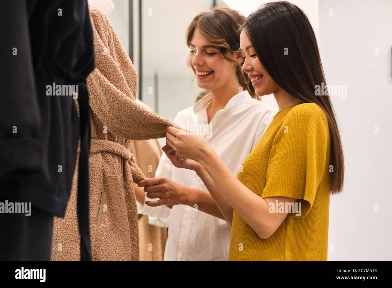 Due ragazze eleganti allegre che scelgono felicemente i vestiti nel deposito di moda Foto Stock