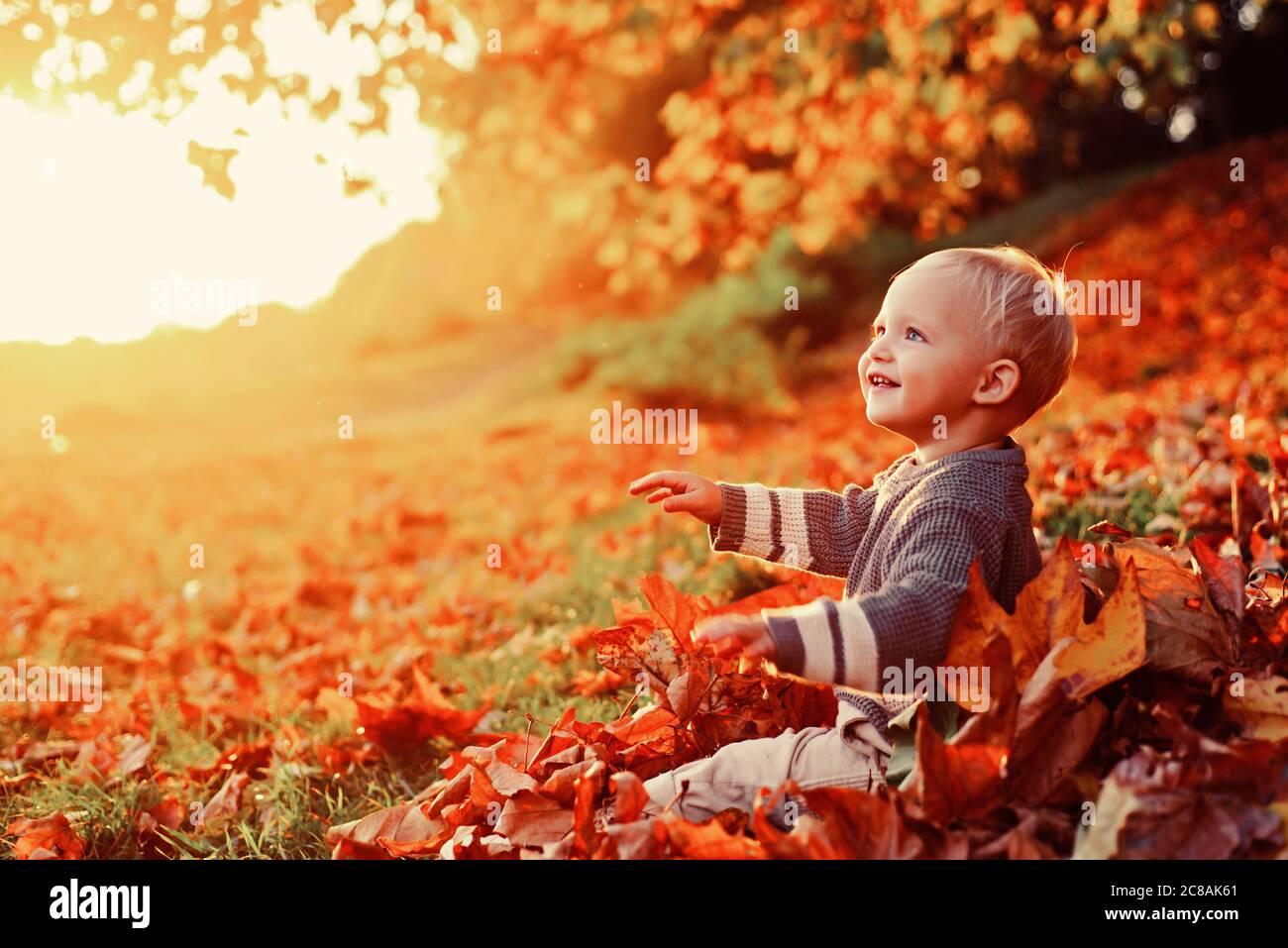 Ricordi d'infanzia. Bambino autunno lascia sfondo. Momenti caldi dell'autunno. Gli occhi blu del bambino godono l'autunno. Piccolo bambino elegante al sole Foto Stock