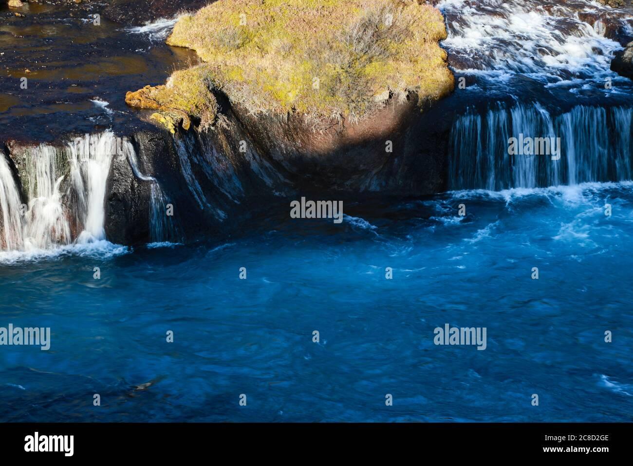 Cascata Bjarnafoss in Islanda, proveniente da sotto una grande pianura lavica. Colori blu incantevoli. Foto Stock