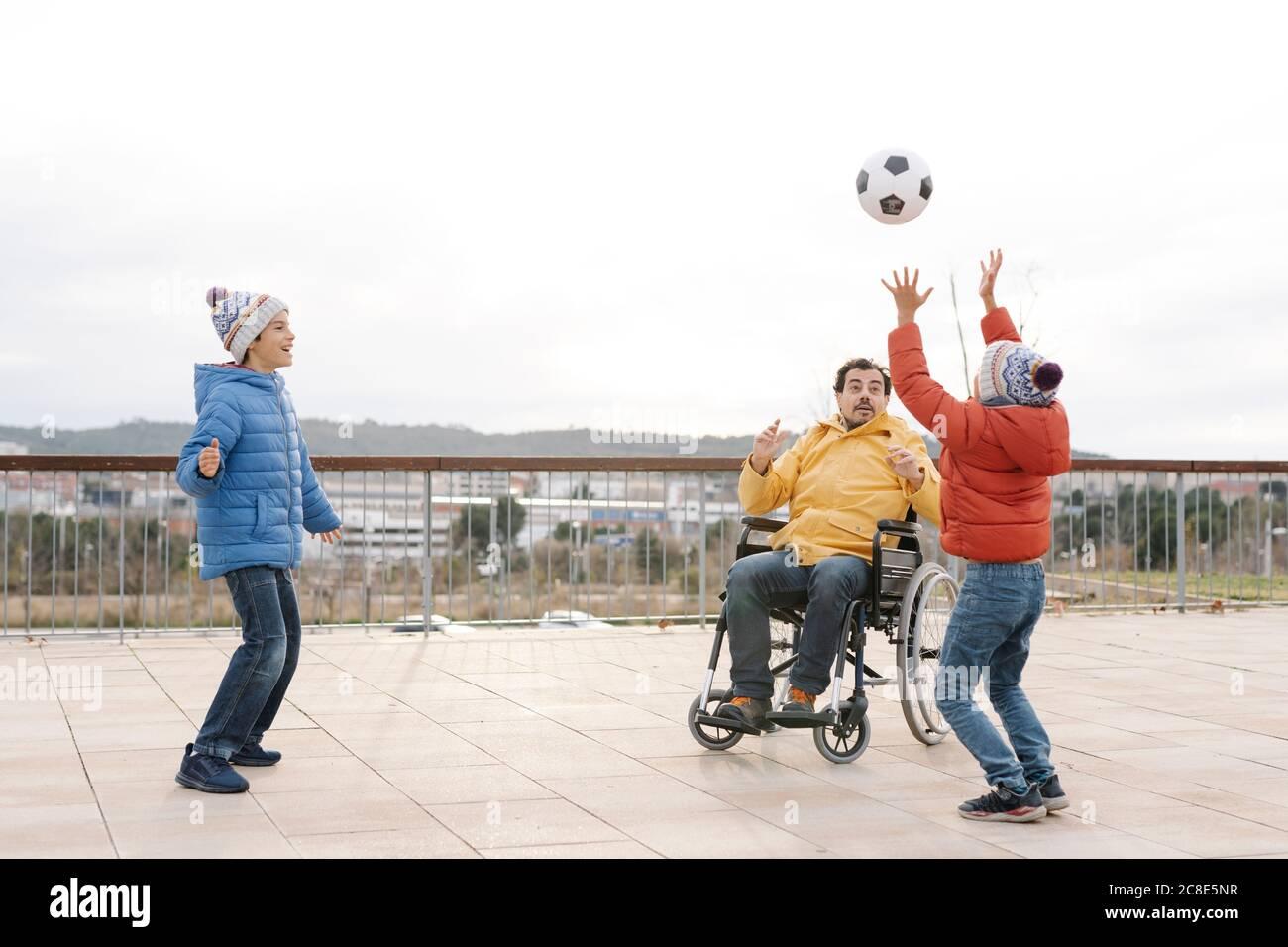 Uomo seduto su sedia a rotelle che lancia la palla verso i figli giocosi dentro parcheggio Foto Stock