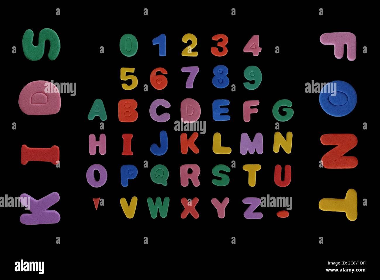 Caratteri per bambini con contatori pieni di caratteri colorati in schiuma, lettere alfabeto e numeri. Foto Stock