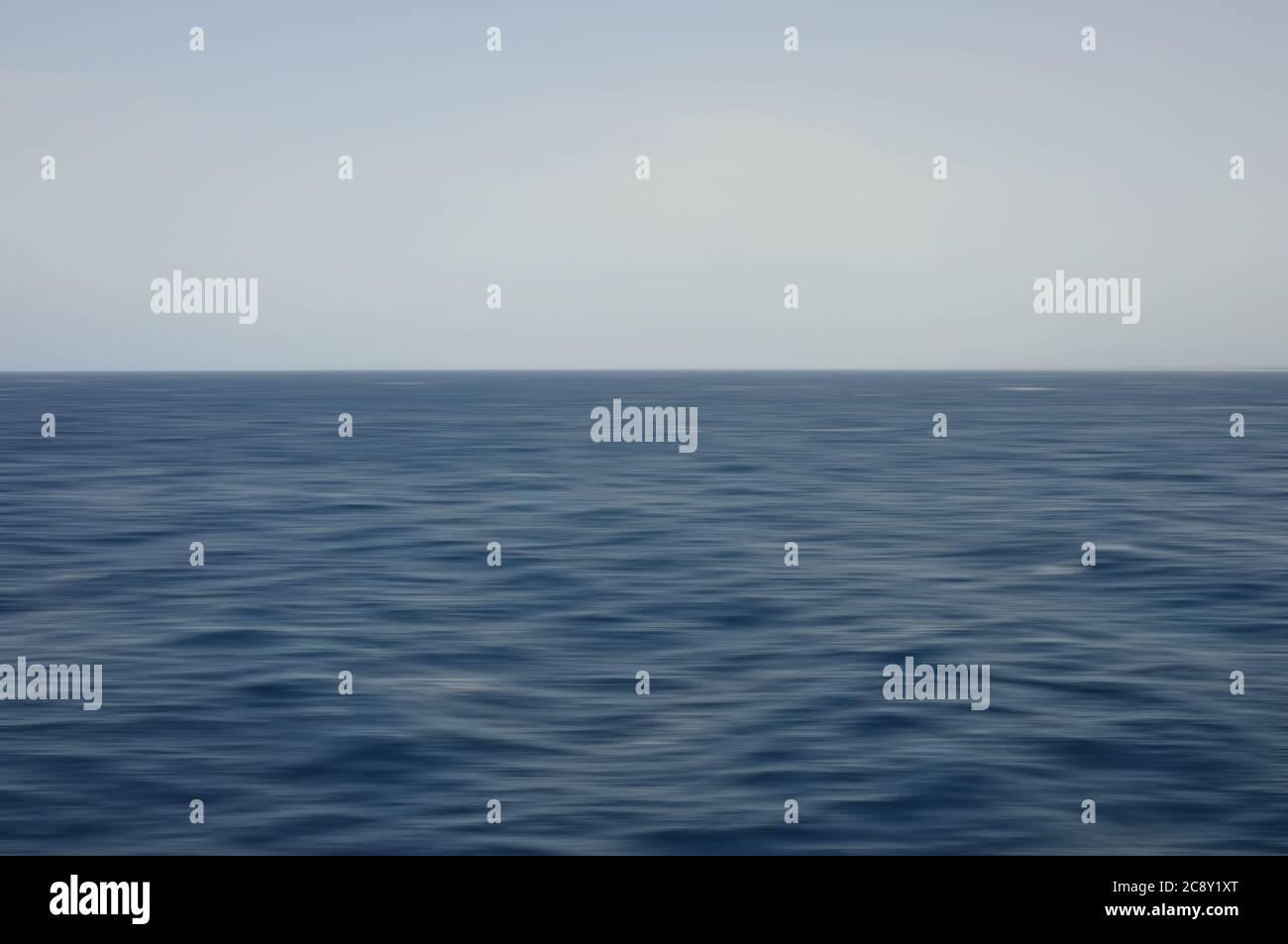 Onde di mare profondo e cielo blu. Sfondo sfocato con movimento astratto. Foto Stock