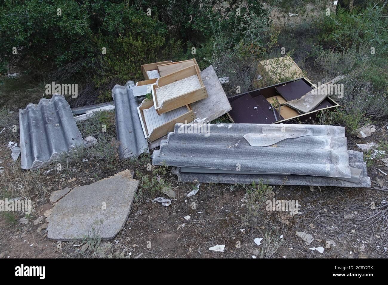 Amianto cemento corrugato tetti fogli e mobili rotti gettati nel legno. Smaltimento improprio di materiale tossico vietato ai rifiuti illegali dum Foto Stock