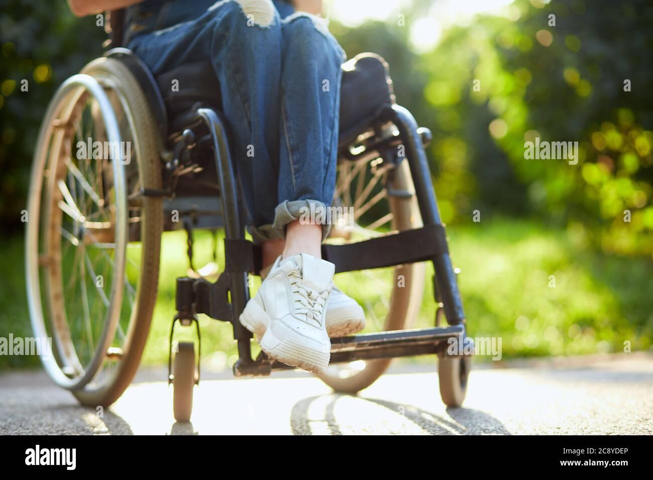 giovane ragazza disabile in tuta e trainer bianchi seduti con gambe incrociate sulla sedia a rotelle. primo piano foto ritagliata. Foto Stock