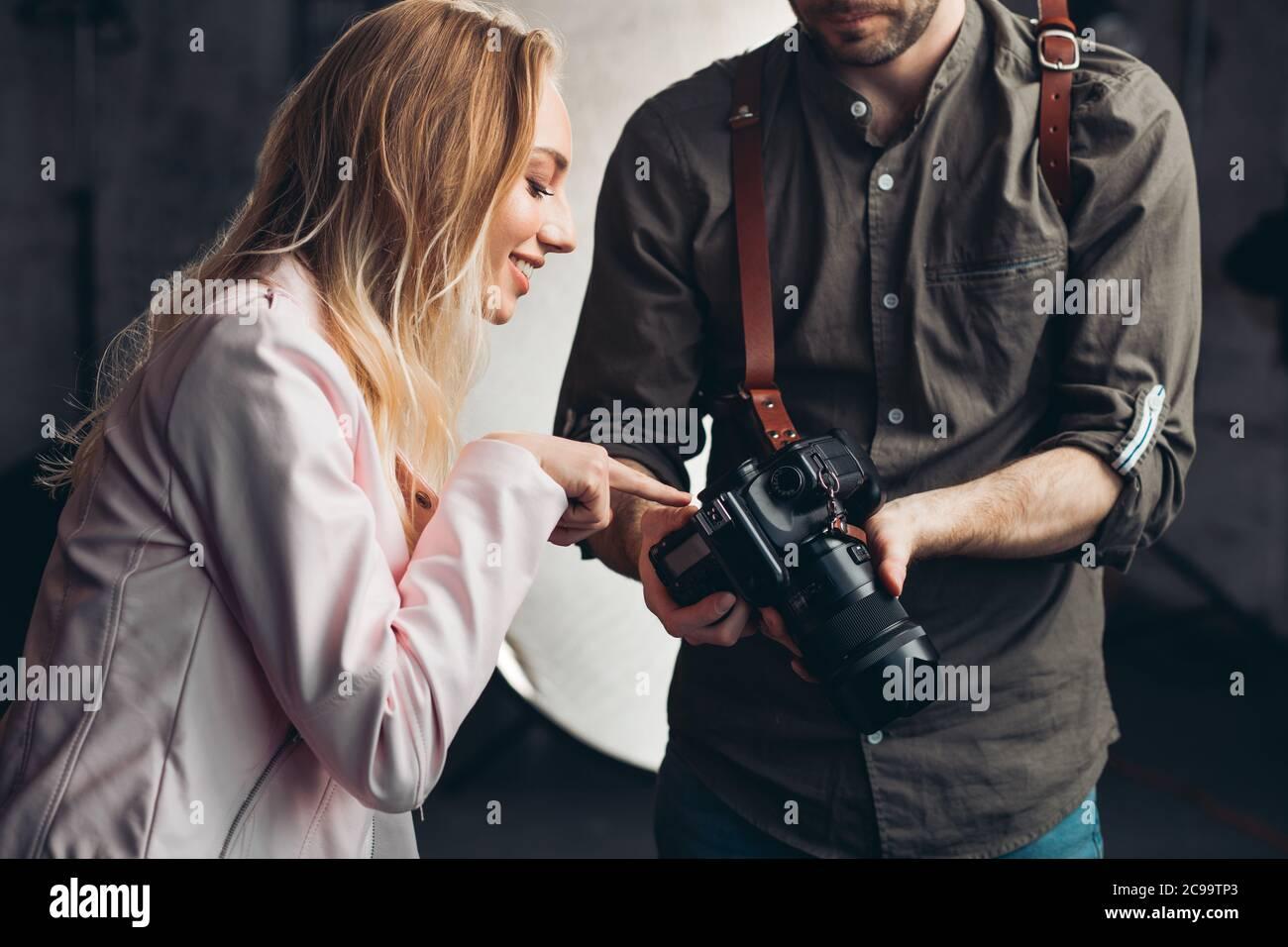 bella ragazza impressionante che punta alla foto mentre lavora con un fotografo, ragazza allegra che dà consigli per il fotografo in studio Foto Stock