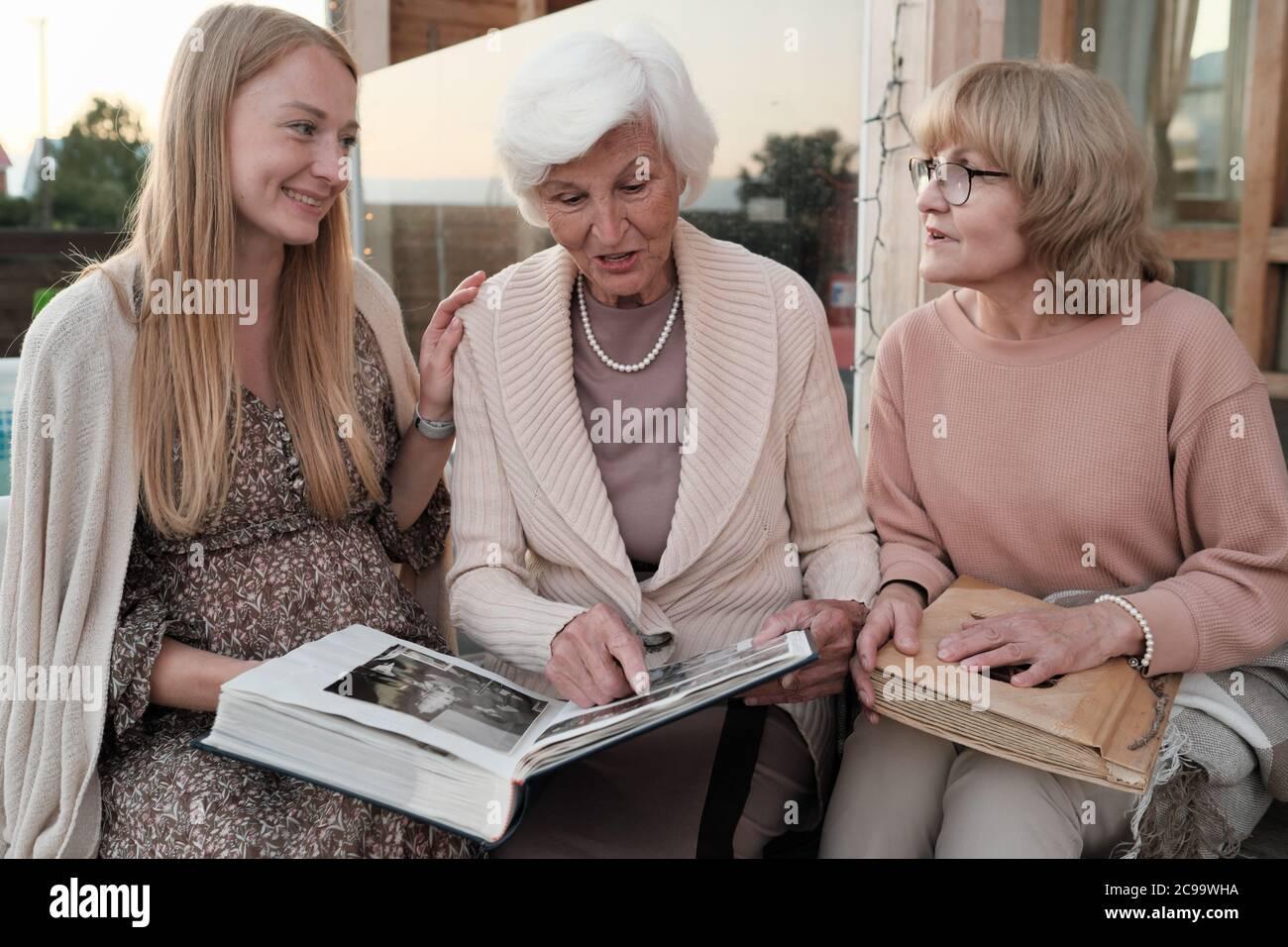 Famiglia di tre seduti all'aperto e guardando insieme album di famiglia ricordano i momenti felici Foto Stock