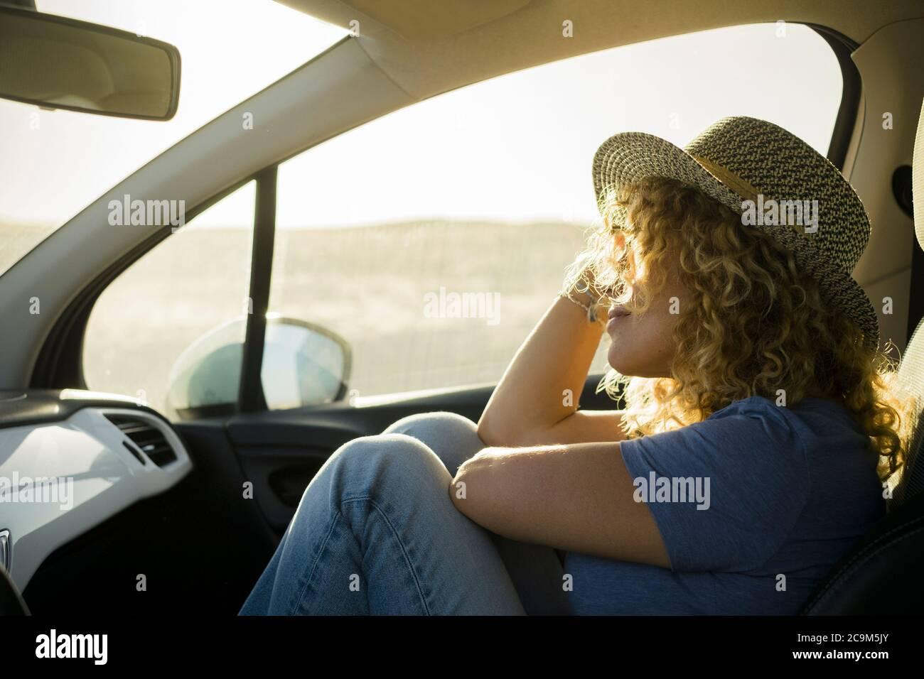 una, bella donna riccia godendo le sue vacanze all'aperto viaggiando con una macchina - tramonto e sole giorno sullo sfondo - persona rilassata e serena Foto Stock