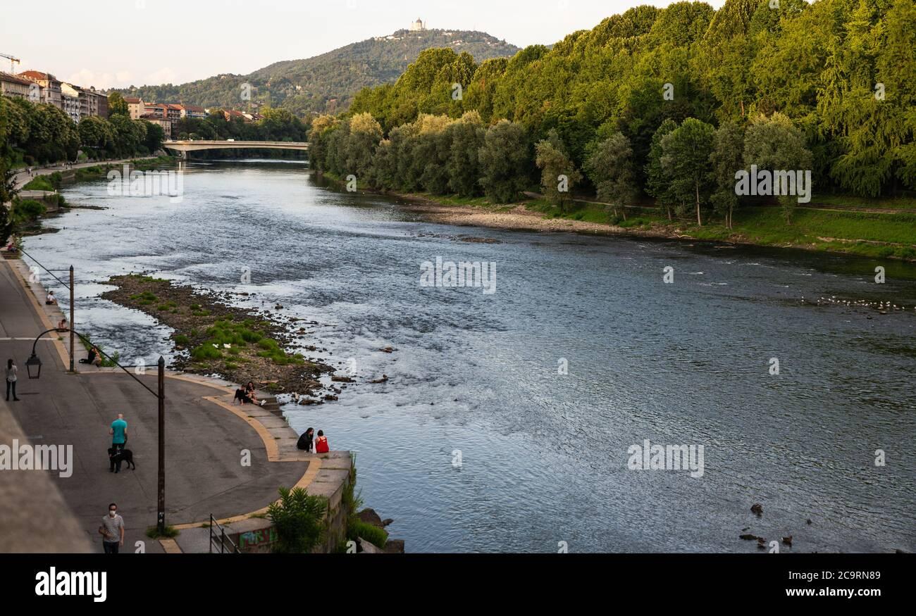 Torino, Piemonte, Italia. Luglio 2020. Splendida vista serale sul fiume po. La gente si rilassa lungo il fiume e il panorama della collina torinese. Foto Stock