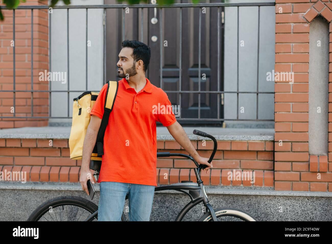 Lavorare in città. Un vero deliveryman con barba con zaino e bicicletta, con smartphone e alla ricerca di indirizzo Foto Stock