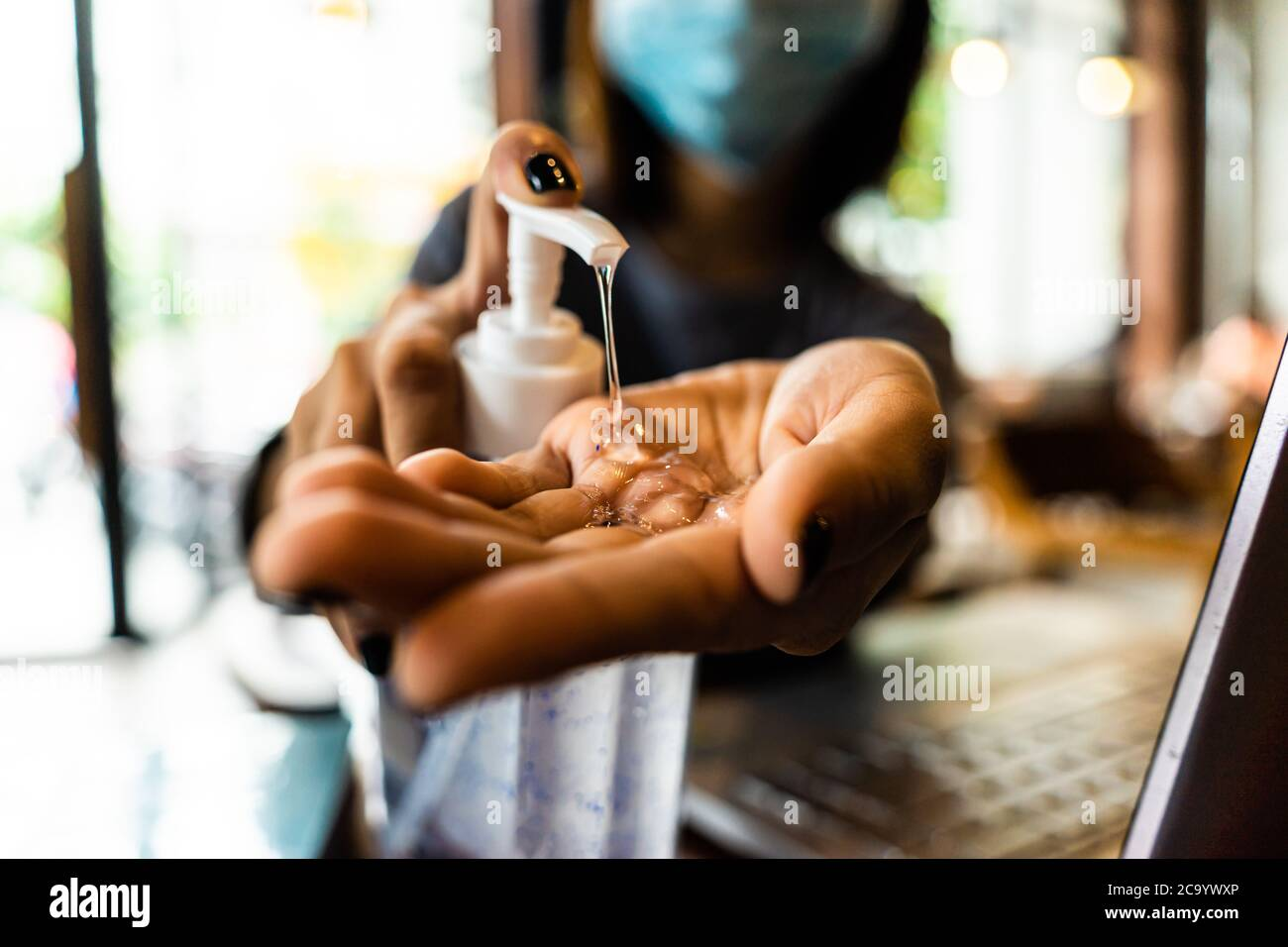 Giovane donna lavando le mani con gel di alcol in quarantena per coronavirus indossare maschera protettiva con distanza sociale e utilizzando computer portatile lavoro Foto Stock