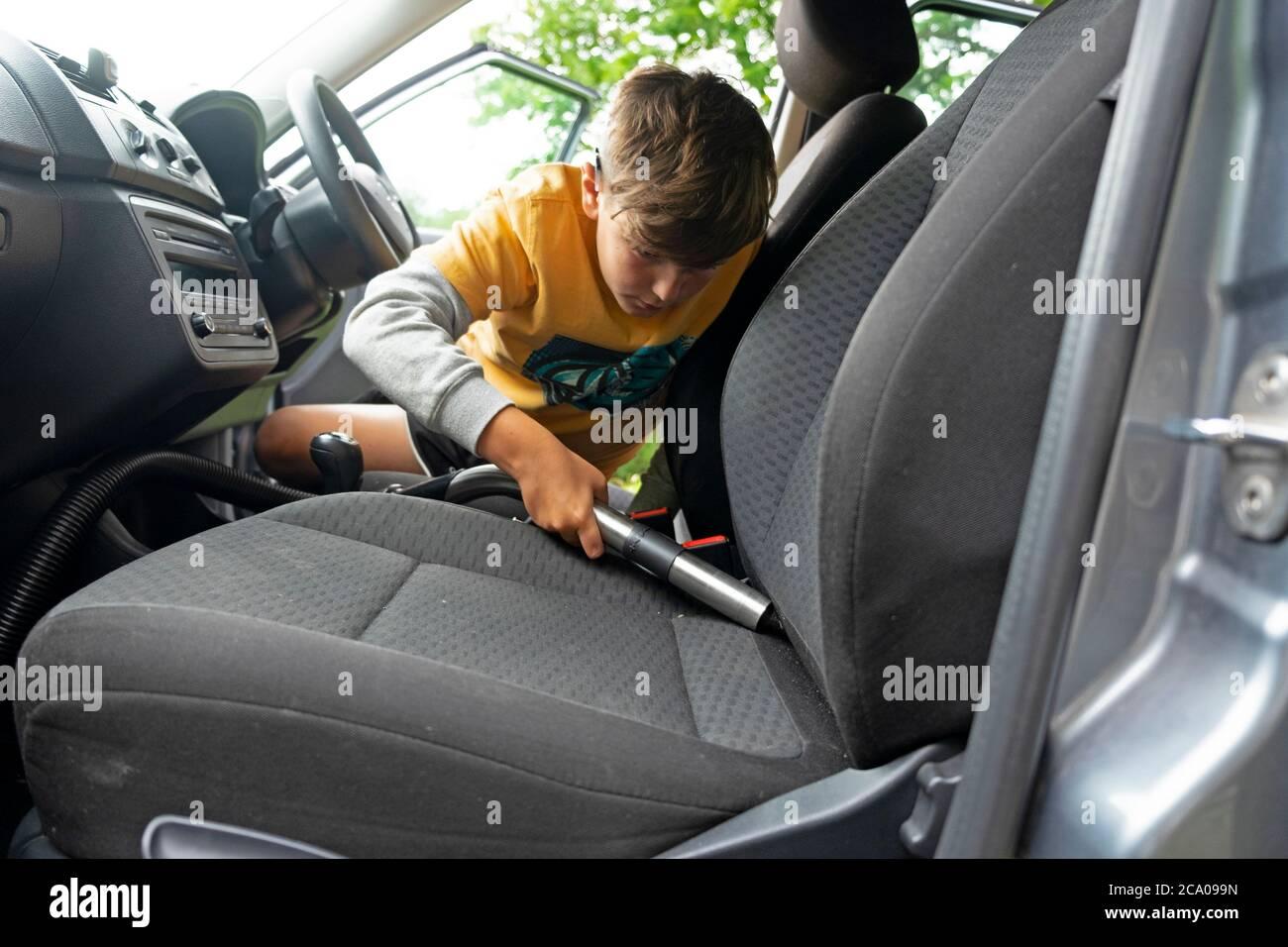 Bambino che fa la tappezzeria di pulizia chore all'interno di una macchina con un aspirapolvere per guadagnare i soldi della tasca durante le vacanze scolastiche estive Galles UK KATHY DEWITT Foto Stock