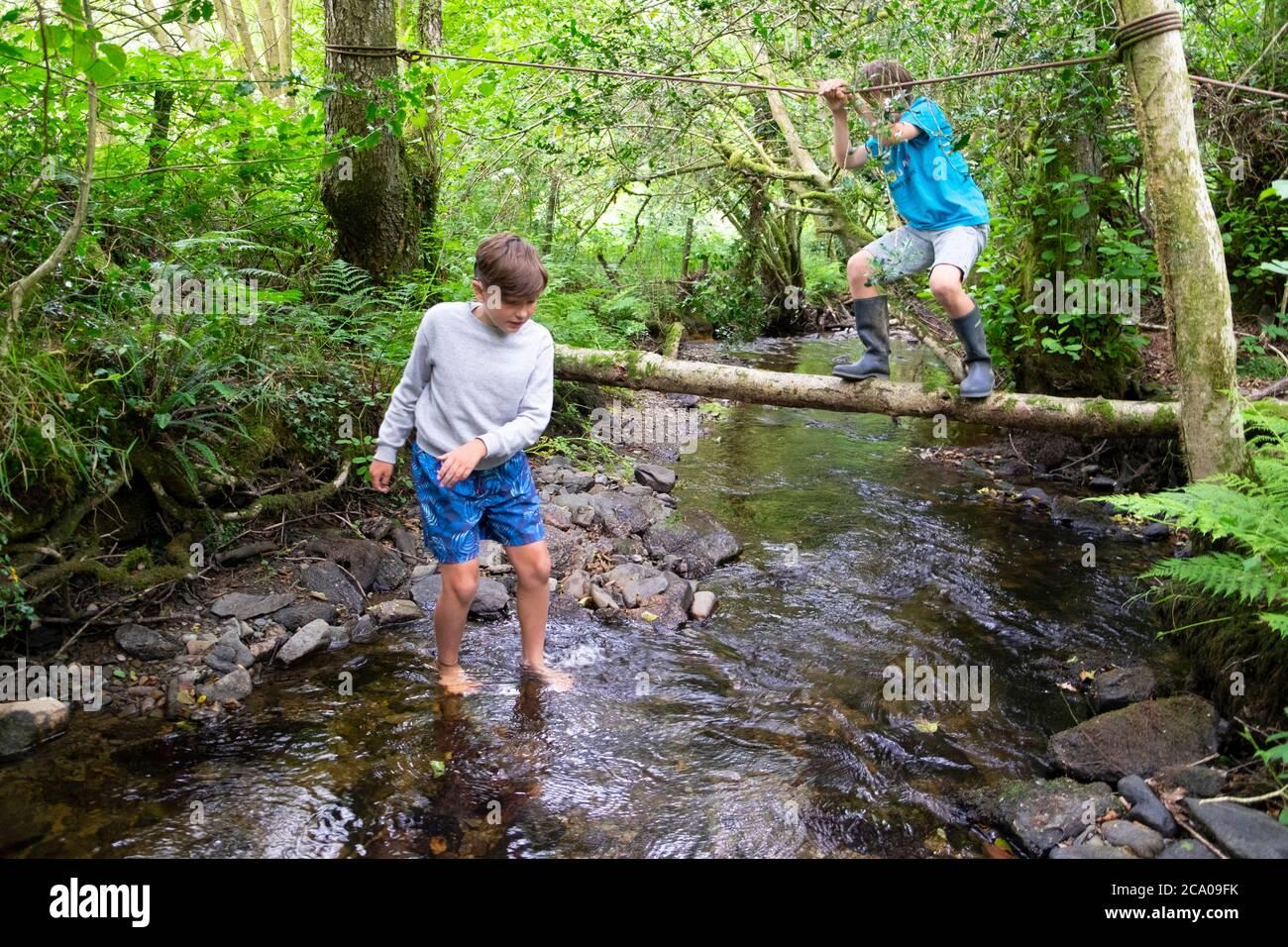 Ragazzi bambini bambini bambini in vacanza estiva dopo aver chiuso i giochi Ruscello in verde campagna boscosa sulla staycation Carmarthenshire Galles UK KATHY DEWITT Foto Stock