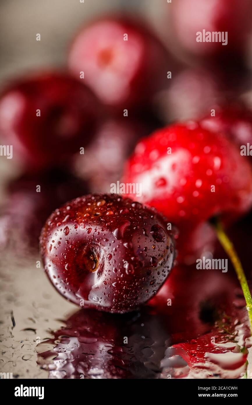 ancora vita di ciliegie rosse e succose su sfondo scuro. Gruppo di ciliegie. Foto Stock