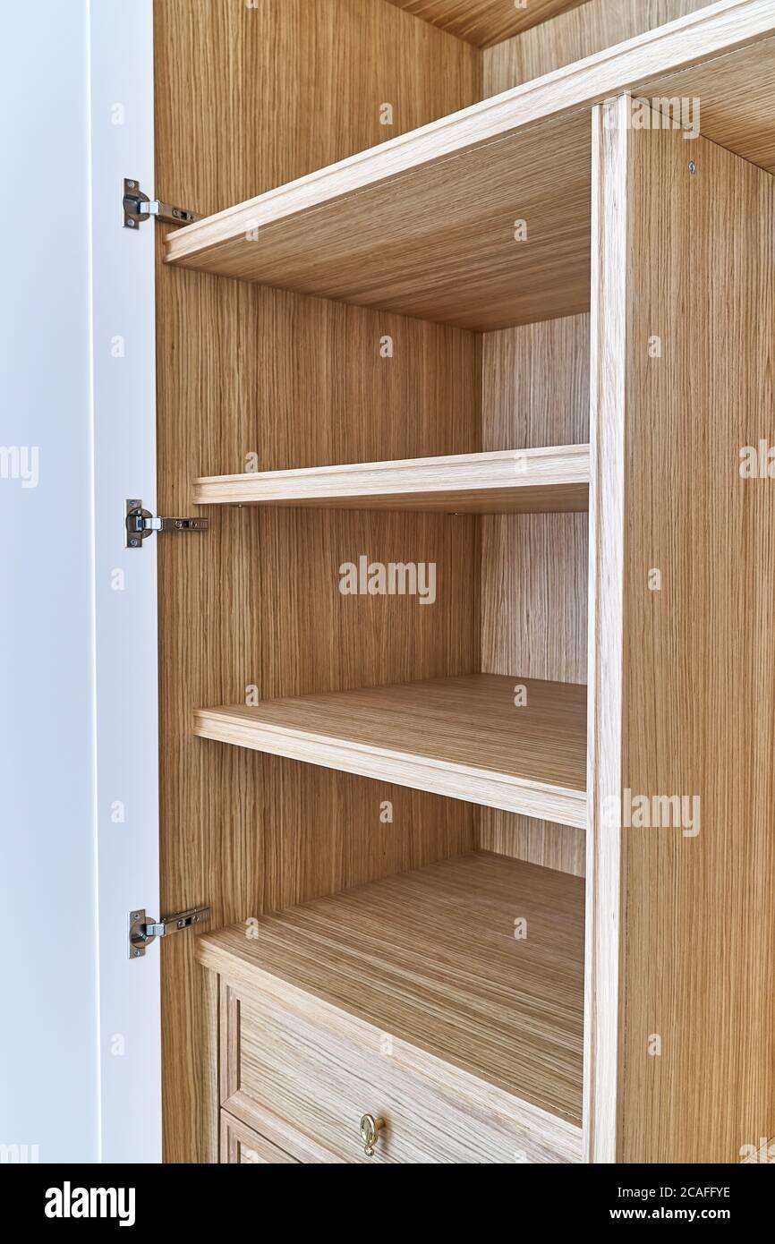 armadio bianco aperto con cassetti e ripiani in legno
