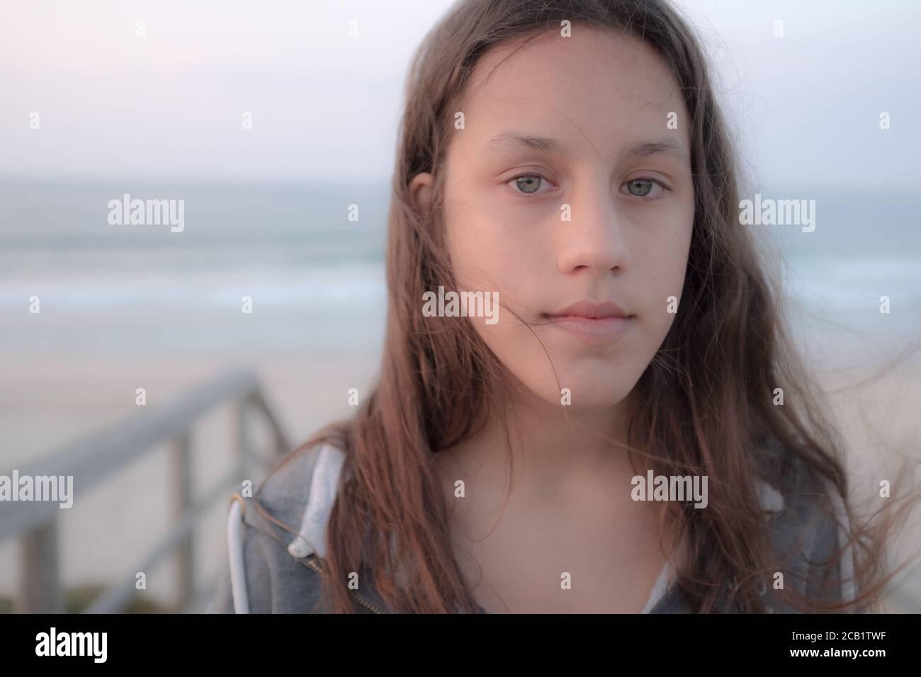 Ritratto di una ragazza adolescente con lunghi capelli marroni e occhi verdi guardando la fotocamera. Donna giovane seria con capelli lunghi e ondulati. Foto Stock