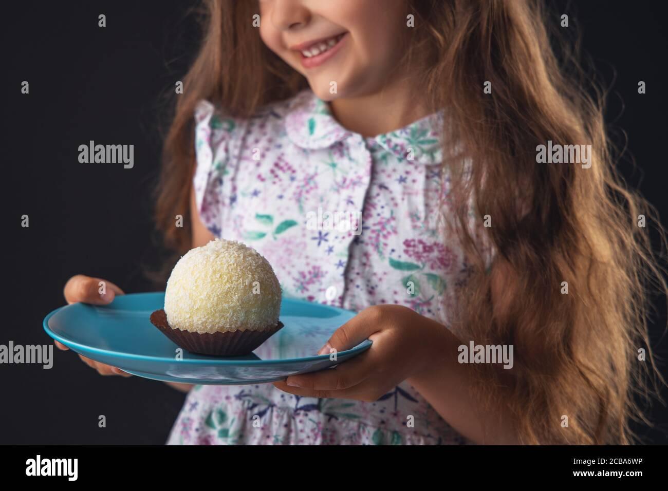 Bella bambina sorpresa da una caramella di cocco al cioccolato grande gustosa come una palla. Capretto pronto a mangiare la torta. Foto Stock