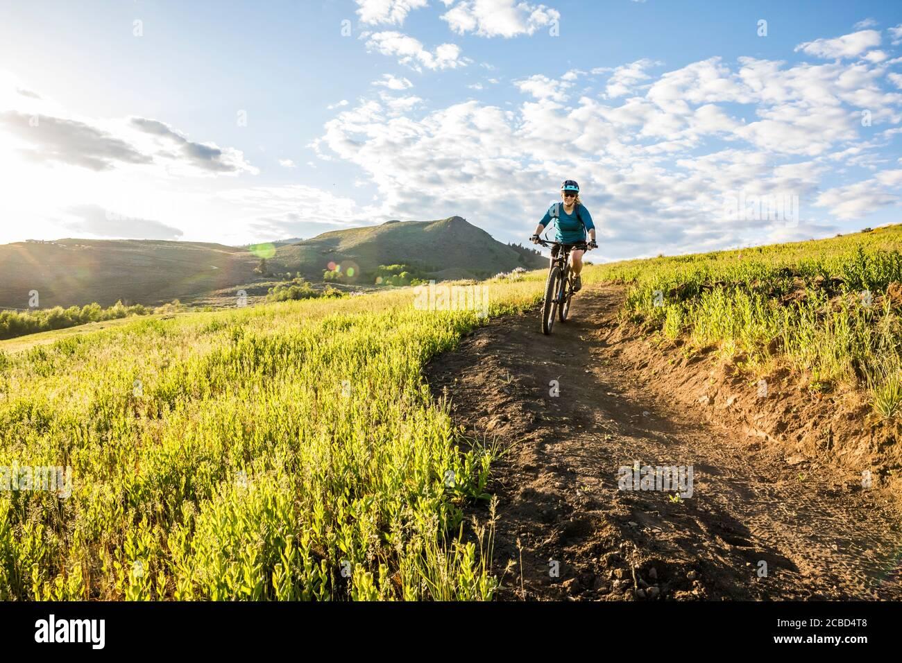 Una donna che sale sul sentiero di Lewis Butte fuori Winthrop, Washington in un pomeriggio soleggiato a maggio. Foto Stock