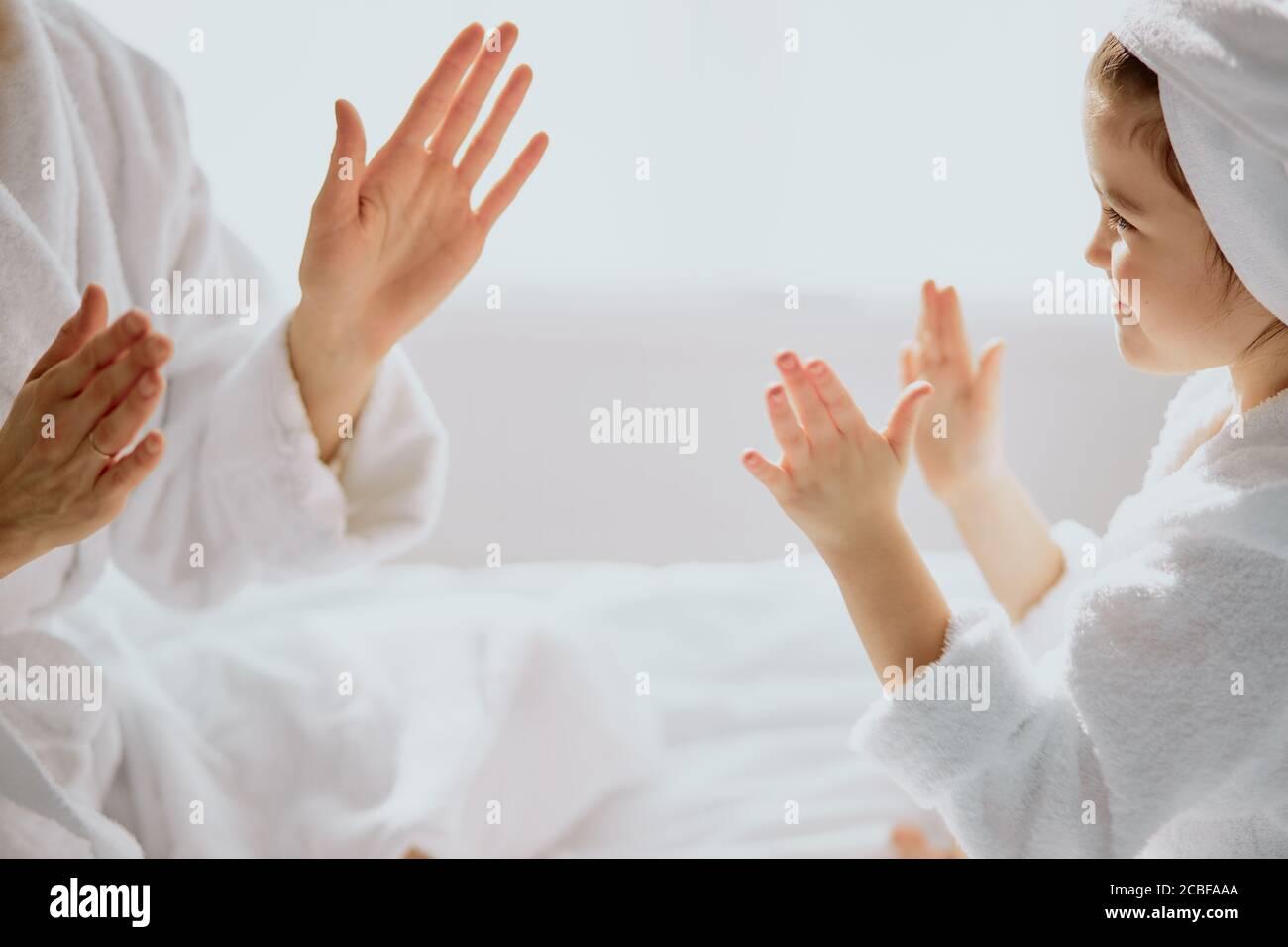 donna caucasica e bambina si siedono giocando a mani aggrappate insieme, famiglia amichevole Foto Stock