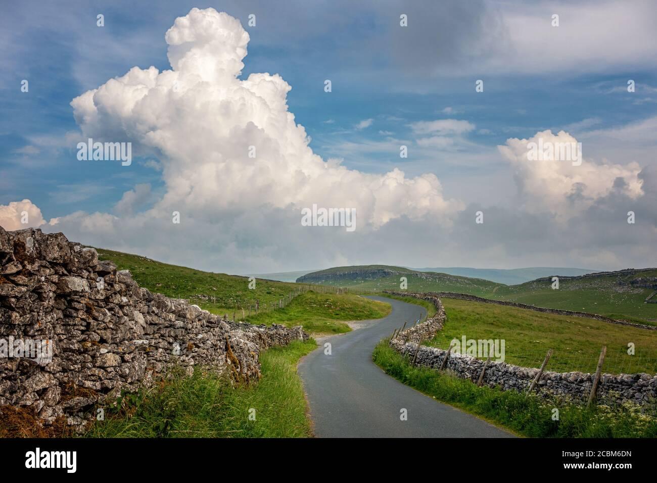 Paesaggi del Regno Unito: Vicolo di campagna in uno splendido scenario nello Yorkshire Dales National Park, dirigendosi sopra Malham Moor con un edificio di tuonnuvole Foto Stock