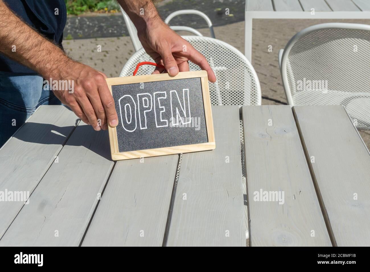 Cartello aperto scritto a mano nelle mani del cameriere sul tavolo del caffè all'esterno. Cartello con le mani aperto nello snack bar all'aperto. Lavagna con iscrizione come sym Foto Stock