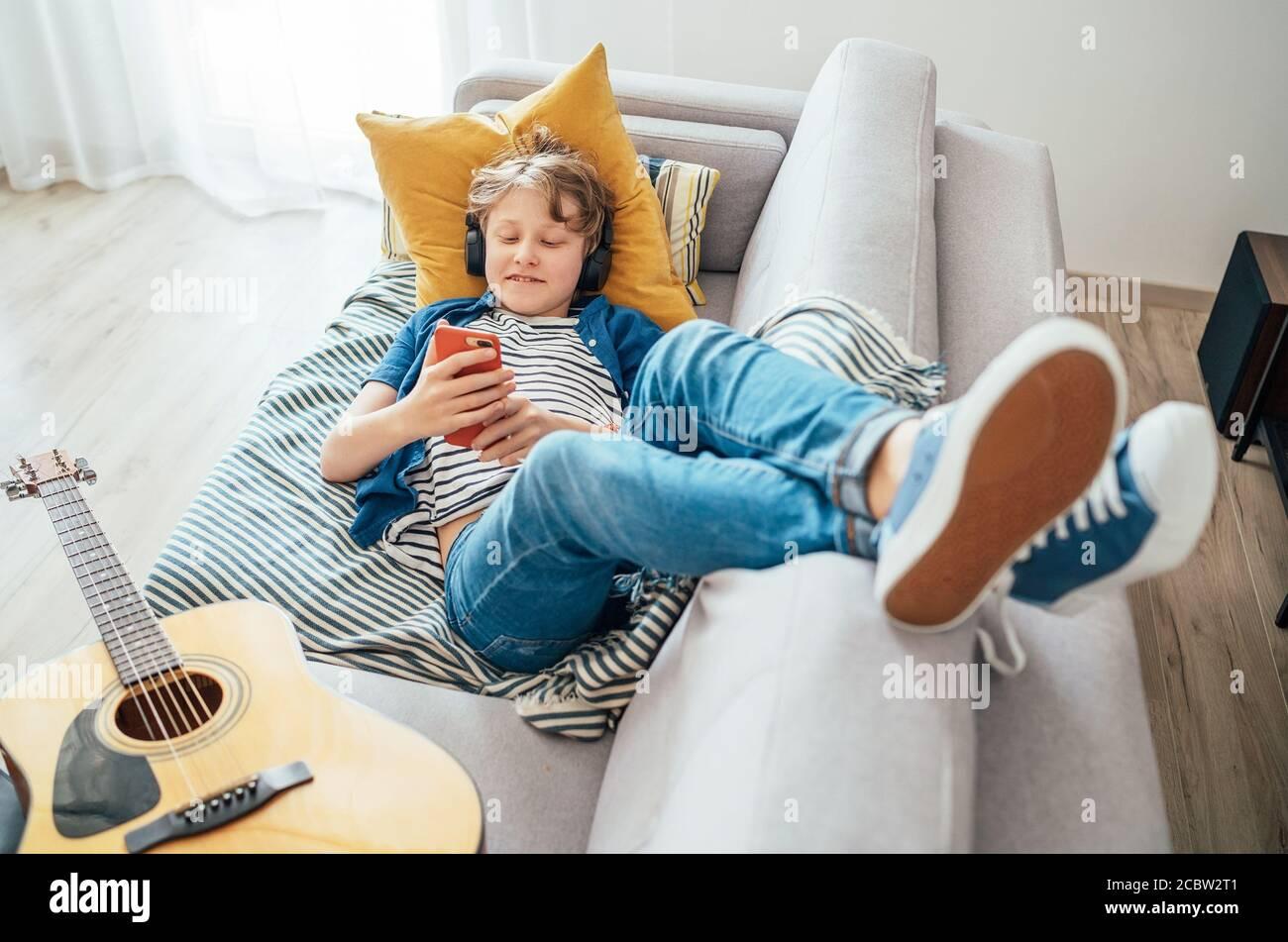 Ragazzo preseno sdraiato con la chitarra su un comodo divano vestito jeans casual e nuove sneakers ascoltare musica e chattare utilizzando cuffie wireless connesse w Foto Stock
