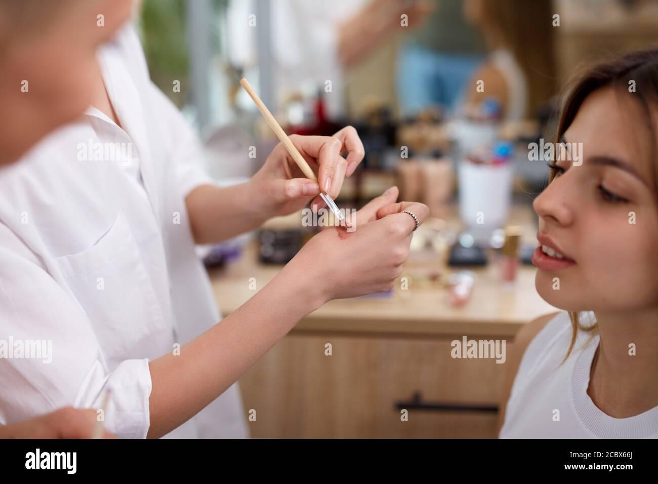 il professionista make-up artista o visagist applica i cosmetici a portata di mano prima di applicarli sul viso, in salone di bellezza Foto Stock