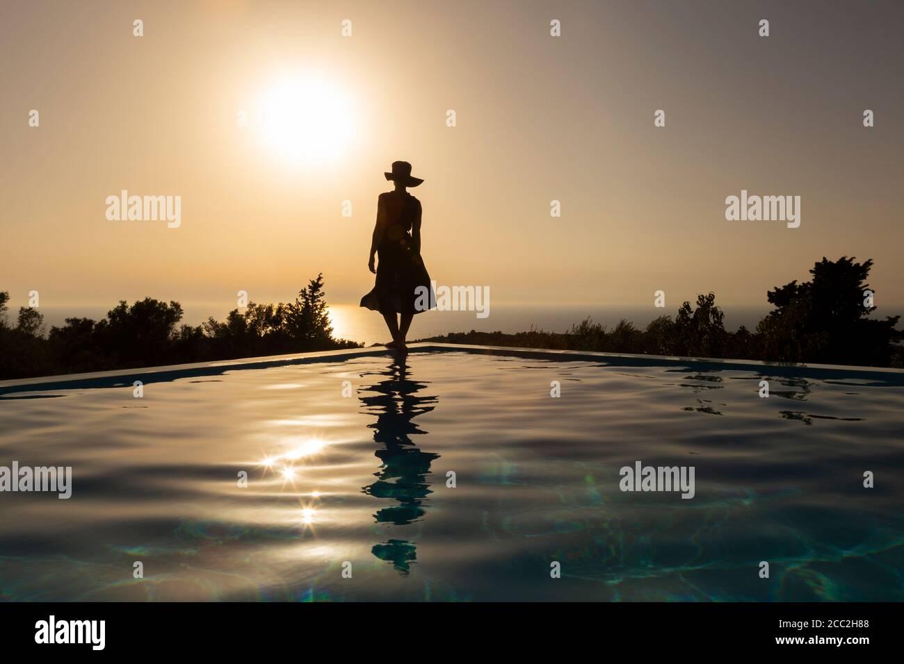 Silhouette di una ragazza che si erge sul bordo di una piscina infinity guardando il tramonto sul mare, Lefkada, Isole IONIE, Grecia Foto Stock