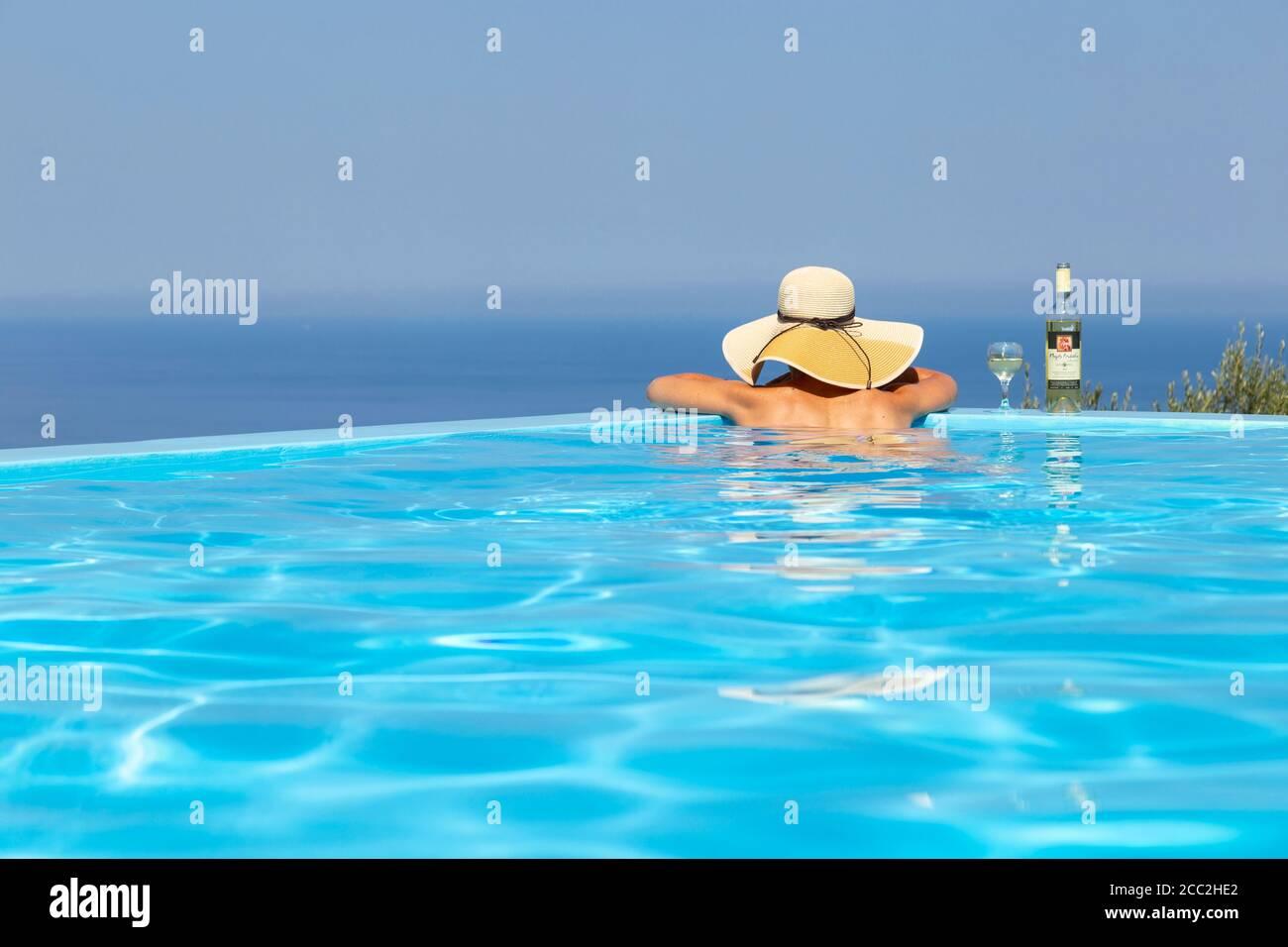Una ragazza in un cappello da sole con una bottiglia di vino poggiata sul bordo di una piscina infinity e guardando verso il mare, Lefkada, Isole IONIE, Grecia Foto Stock