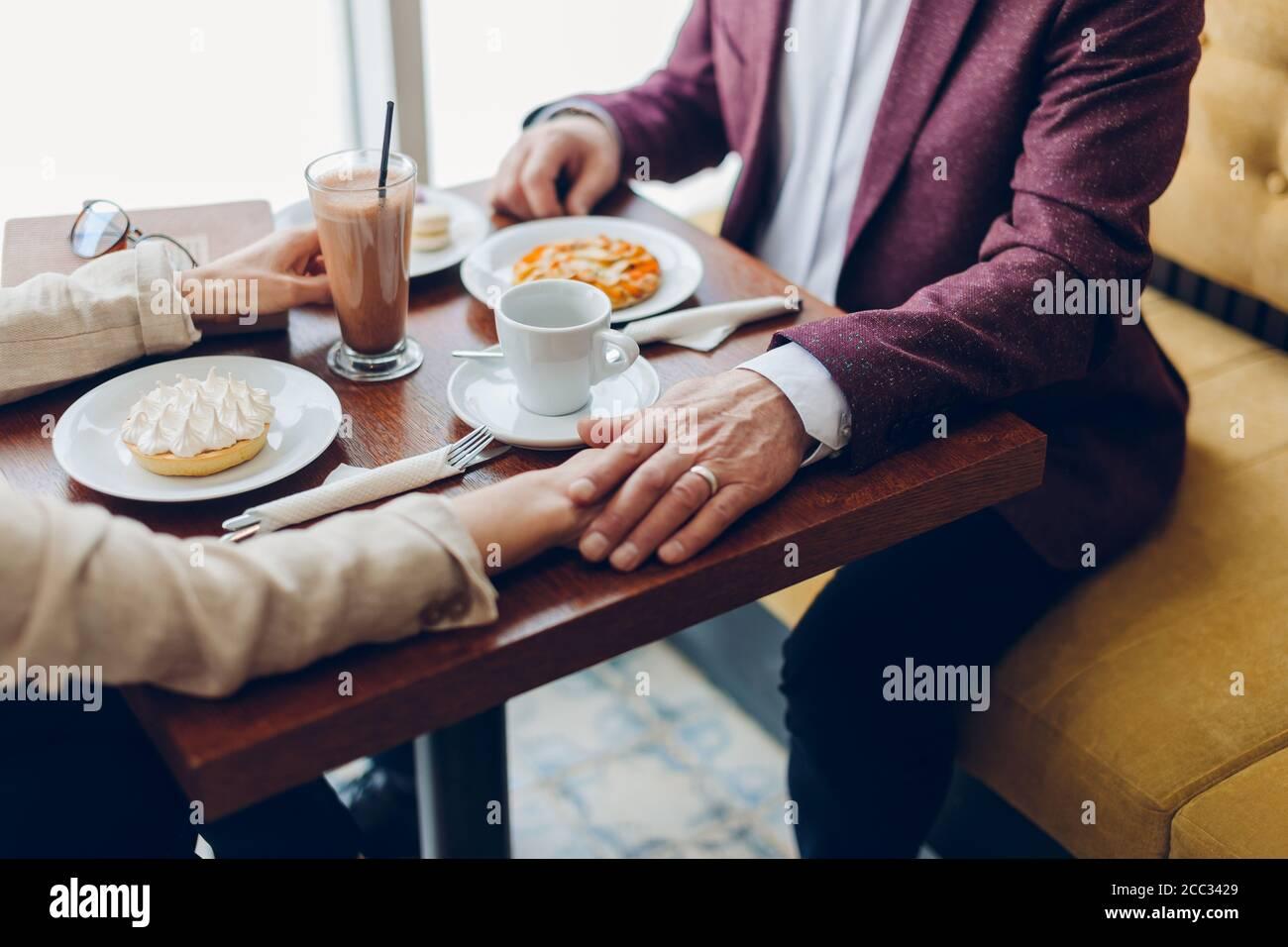 uomo anziano che tiene la mano della moglie mentre si siede nel caffè. uomo che sostiene la sua donna in una situazione difficile, coppia che supera i problemi della famiglia Foto Stock