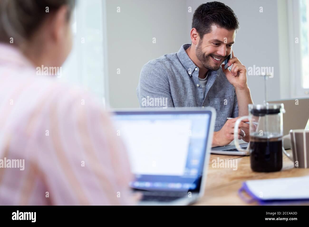 Coppia di affari che lavora da casa seduta al tavolo durante Pandemic Blocco tramite telefono cellulare Foto Stock