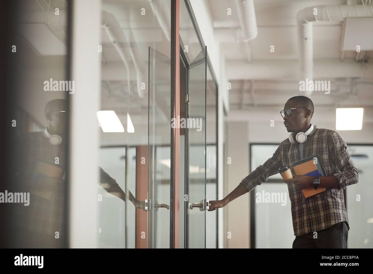 Giovane africano in abbigliamento casual che apre la porta di sala del consiglio che viene alla riunione Foto Stock