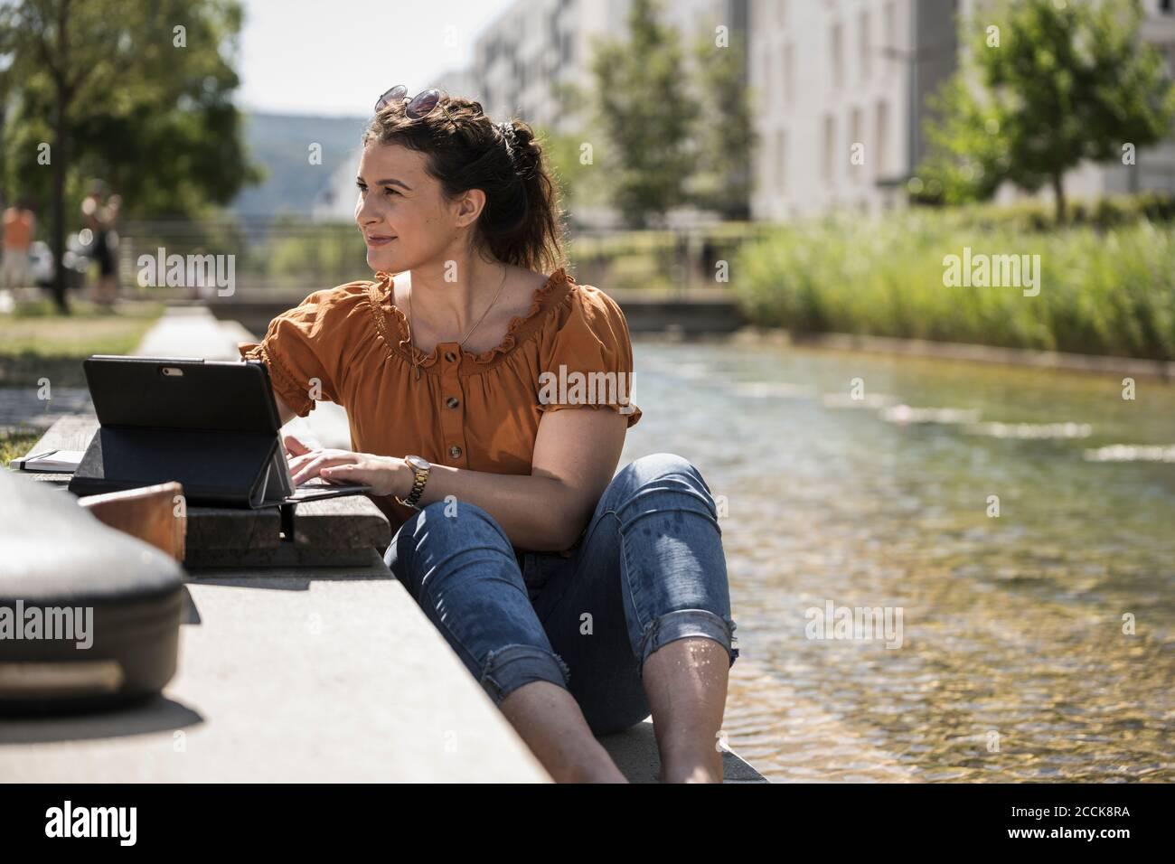 Donna premurosa con computer portatile seduto accanto al laghetto nel parco durante giorno di sole Foto Stock