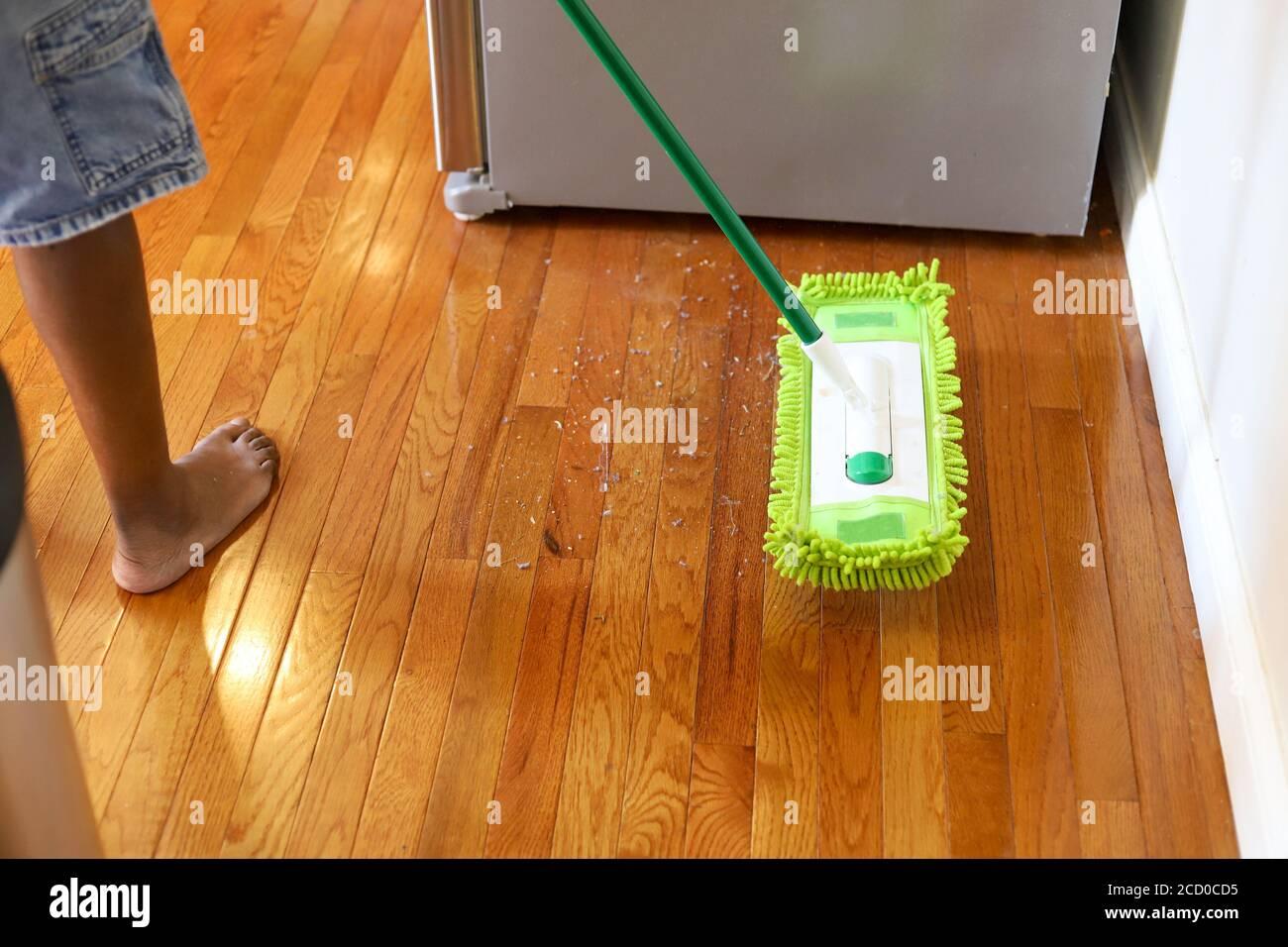 Un uomo afroamericano che spolvera il pavimento di legno duro in una cucina residenziale Foto Stock